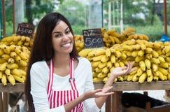 拉丁美洲的女推销员在提出香蕉的农夫市场上 库存照片