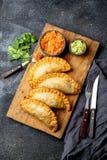 拉丁美洲的油煎的empanadas用蕃茄和鲕梨调味汁 顶视图 图库摄影