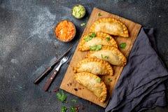 拉丁美洲的油煎的empanadas用蕃茄和鲕梨调味汁 顶视图 免版税图库摄影