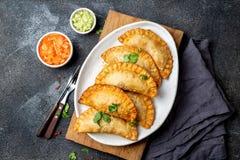 拉丁美洲的油煎的empanadas用蕃茄和鲕梨调味汁 顶视图 免版税库存图片