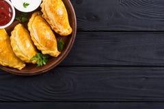 拉丁美洲的被烘烤的牛肉empanadas用调味汁 免版税库存照片