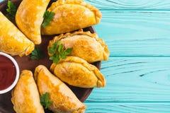 拉丁美洲的被烘烤的牛肉empanadas用调味汁 库存照片