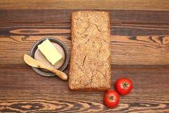 拉伊家制面包用两个蕃茄和黄油片断在木桌上的 库存照片