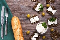 拉伊油煎方型小面包片用木表面上的软干酪,顶视图 一把大面包和叉子与一把刀子在一块绿色餐巾 库存照片