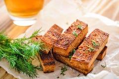 拉伊油煎方型小面包片用莳萝和一杯啤酒 免版税库存照片