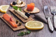 拉伊薄脆饼干和薄脆饼干用乳酪和红色鱼在一张木桌上 选择聚焦 库存照片