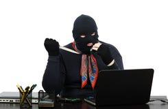 巴拉克拉法帽的强盗有刀子的谈话在手机 免版税库存图片