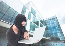 巴拉克拉法帽的犯罪人在玻璃大厦前面的膝上型计算机 库存照片