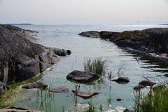 拉多加湖岩石岸  在水外面是岩石和植物 有天际的许多海岛 清楚的晴天 免版税库存照片
