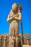 拉姆西斯雕象II与他的在阿蒙镭(卡纳克神庙寺庙寺庙的女儿优点阿门在卢克索) 库存照片