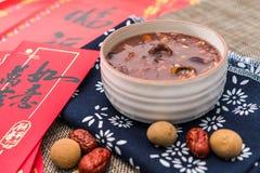 拉巴粥,Babao粥,在北ChinaLaba粥的一个食家盘在对联红色信封下背景  库存照片