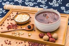 拉巴粥,Babao粥,在北ChinaLaba粥的一个食家盘在对联红色envelopeLaba porr下背景  免版税库存照片