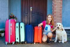 拉布拉多狗女孩孩子行李蓝色桃红色橙色房子太阳夏天行李家用汽车准备好假日种植绿色四 库存照片