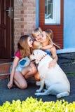 拉布拉多狗母亲女儿太阳宠物草夏天公园笑白肤金发的少年nurseling的夏天的家太阳 库存照片
