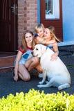 拉布拉多狗母亲女儿太阳宠物草夏天公园笑白肤金发的少年nurseling的夏天的家太阳 免版税库存图片