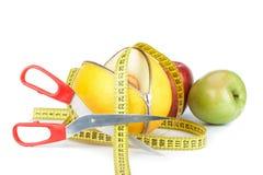 拉开拉链的瓜、苹果和测量的磁带 免版税库存照片