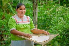 拉戈阿格里奥,厄瓜多尔- 2016年11月, 17 :妇女在Siona的一个室外厨房里展示烹调丝兰玉米粉薄烙饼 免版税图库摄影