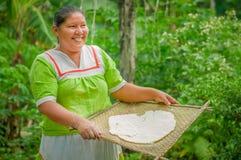 拉戈阿格里奥,厄瓜多尔- 2016年11月, 17 :妇女在Siona的一个室外厨房里展示烹调丝兰玉米粉薄烙饼 免版税库存照片