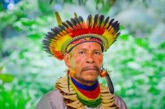 拉戈阿格里奥,厄瓜多尔- 2016年11月17日:一个Siona僧人的画象传统礼服的有在的一个羽毛帽子的 库存图片