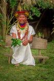 拉戈阿格里奥,厄瓜多尔- 2016年11月17日:传统礼服的Siona僧人有一个羽毛帽子的在一个土产村庄 免版税库存照片