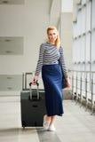 拉扯一个大手提箱的一件镶边夹克的旅游女孩金发碧眼的女人在驻地 可爱的女孩运载一个手提箱 免版税库存照片