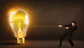 拉扯一个大明亮的发光的电灯泡的商人 免版税库存照片