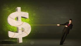 拉扯一个大绿色美元的符号的商人 免版税库存图片