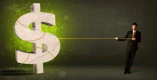 拉扯一个大绿色美元的符号的商人 库存照片