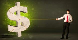 拉扯一个大绿色美元的符号的商人 库存图片