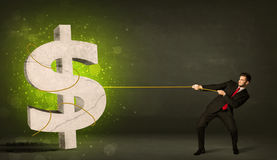 拉扯一个大绿色美元的符号的商人 免版税库存照片