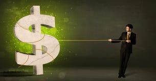 拉扯一个大绿色美元的符号的商人 图库摄影