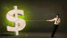 拉扯一个大绿色美元的符号的商人 免版税图库摄影