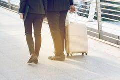 拉扯一个手提箱的商人和女实业家在一个大城市 库存图片