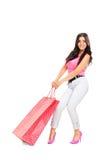 拉扯一个重的购物袋的可爱的女孩 免版税库存照片