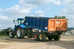 拉扯一辆拖车的现代蓝色拖拉机在农场 免版税库存照片