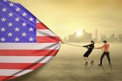 拉扯一面美国国旗的两买卖人 免版税库存图片