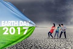 拉扯世界地球日横幅的人们 免版税库存照片