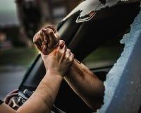 拉扯从汽车的残破的窗口的人另一个人 库存图片