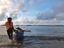 拉扯他的在海滩上的渔夫小船在钓鱼以后 库存照片