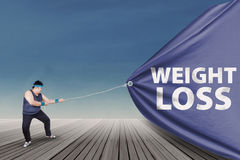 拉扯减重横幅1的肥胖人 免版税库存照片