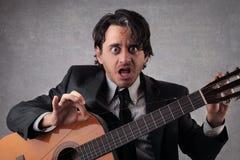 拉扯吉他的串的吃惊的商人 免版税库存照片