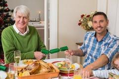 拉扯圣诞节薄脆饼干的微笑的祖父和父亲 图库摄影