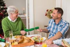 拉扯圣诞节薄脆饼干的祖父和父亲 免版税库存图片
