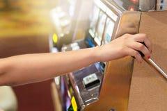 拉扯在一台老虎机的妇女把柄在赌博娱乐场 免版税图库摄影
