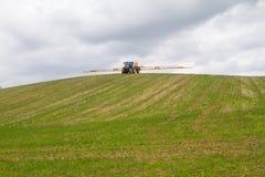 拉扯在小山的蓝色现代拖拉机一台庄稼喷雾器 免版税图库摄影
