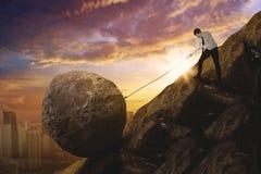 拉扯在峭壁的白种人商人一个岩石 库存照片