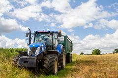 拉扯在收获领域的现代蓝色拖拉机一辆拖车 库存照片