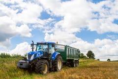 拉扯在收获领域的现代蓝色拖拉机一辆拖车 免版税库存图片