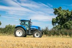 拉扯在收获领域的现代蓝色拖拉机 免版税库存照片