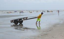 拉扯在海滩的泰国人一辆人力车是拉差 免版税库存图片